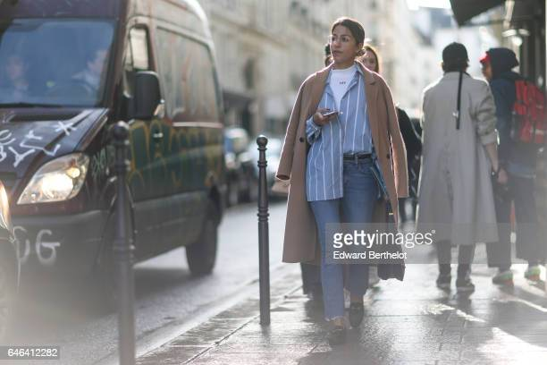 A guest wears a beige coat a white top a blue striped shirt blue denim jeans outside the AALTO show during Paris Fashion Week Womenswear Fall/Winter...