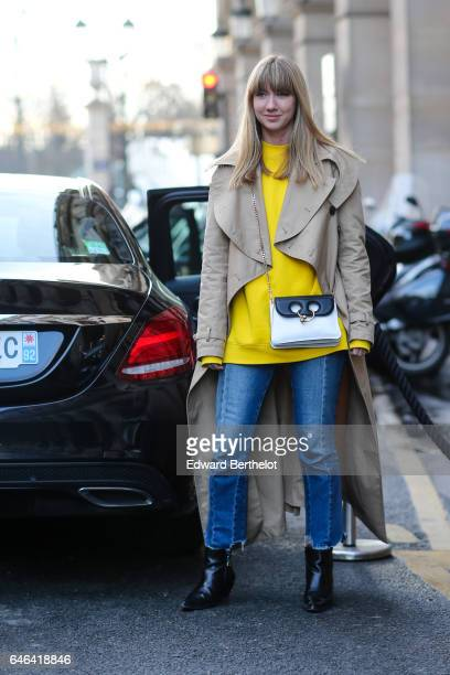 A guest wears a beige coat a yellow top a black and white bag blue denim jeans pants and black leather shoes during Paris Fashion Week Womenswear...