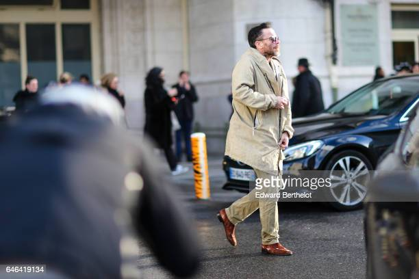 A guest wears a beige coat beige pants and brown shoes outside the Olivier Theyskens show during Paris Fashion Week Womenswear Fall/Winter 2017/2018...