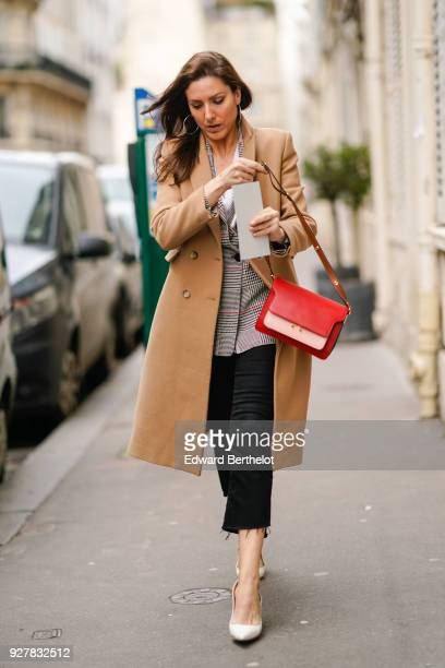 A guest wears a beige coat cropped pants a red bag outside APC during Paris Fashion Week Womenswear Fall/Winter 2018/2019 on March 5 2018 in Paris...