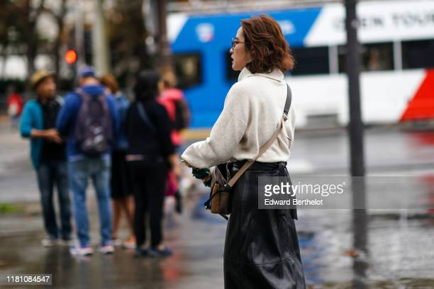 A guest wears a beige cowl collar oversized sweater a brown bag a black leather skirt outside Chanel during Paris Fashion Week Womenswear Spring...