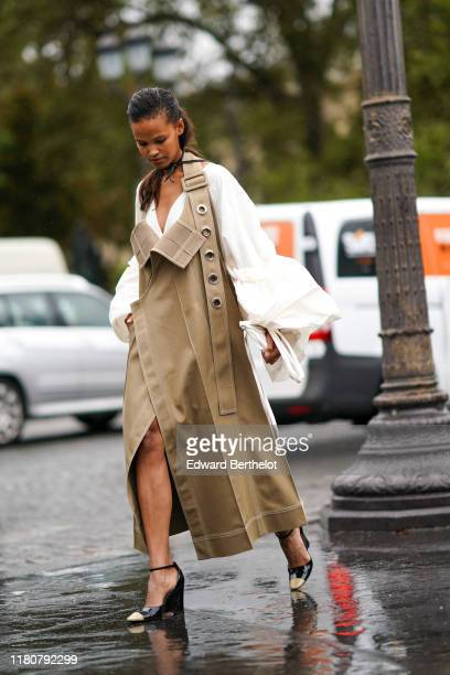 Guest wears a beige dress a white top with oversized sleeves, black shoes, outside Chanel, during Paris Fashion Week - Womenswear Spring Summer 2020,...