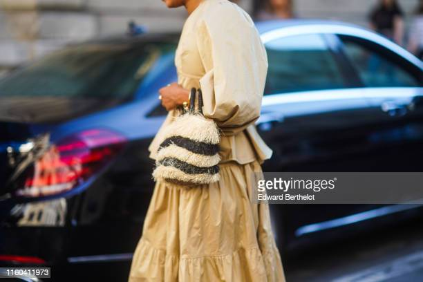 A guest wears a beige dress and a fluffy striped bag outside Valentino during Paris Fashion Week Haute Couture Fall/Winter 2019/2020 on July 03 2019...