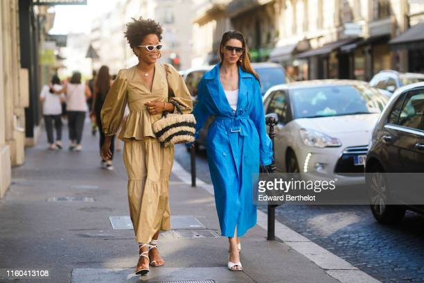 Guest wears a beige dress and a striped fluffy bag ; a guest wears a blue dress trench coat, a white top, a black bag, outside Valentino, during...