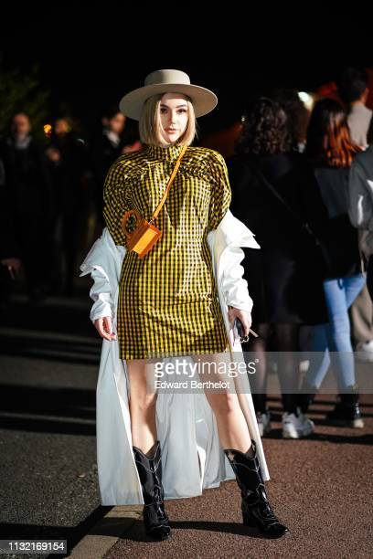 A guest wears a beige hat a yellow and black checkered dress a yellow and orange Jacquemus handbag a white trench coat black cowboy boots outside...