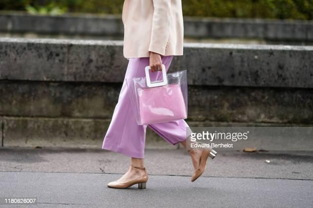 Guest wears a beige jacket, light mauve wide-legs crop pants, a transparent vinyl bag with a light pink clutch inside, nude-color ankle-strap shoes...
