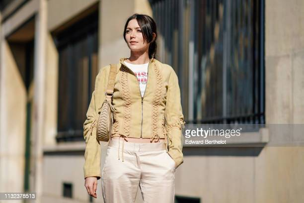 A guest wears a beige jacket with lace a Dior bag flare shiny pants a tshirt outside Dior during Paris Fashion Week Womenswear Fall/Winter 2019/2020...