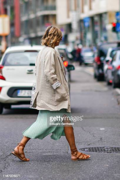 Guest wears a beige linen oversized jacket, a green side-slit skirt, brown leather gladiator flat sandals, outside the Sportmax show during Milan...