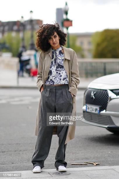 Guest wears a beige long coat, a floral print shirt, gray pants, white sneakers, outside Louis Vuitton, during Paris Fashion Week - Womenswear Spring...