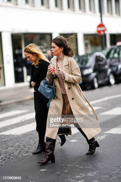 Guest wears a beige long coat, a wool turtleneck pullover, a blue Loewe bag, leather crocodile pattern pointy boots, holds a botlle of Coca Cola...