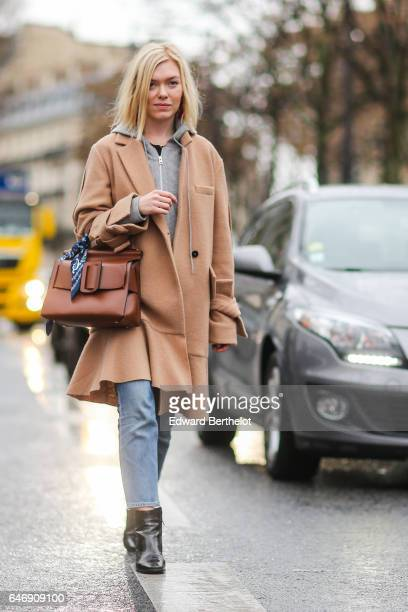 A guest wears a beige long coat and a gray sweater outside the Rochas show during Paris Fashion Week Womenswear Fall/Winter 2017/2018 on March 1 2017...