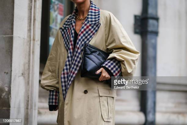 Guest wears a beige long overiszed trench coat with red and blue checked inner lining, a black leather puff bag, during London Fashion Week Fall...