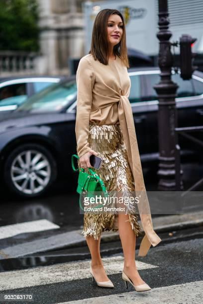 A guest wears a beige long tie top a glossy golden fringe front slit skirt a green handbag offwhite pumps outside Balmain during Paris Fashion Week...