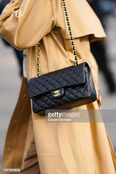 Guest wears a beige long trench coat, a black leather Chanel bag, outside Chanel, during Paris Fashion Week - Womenswear Spring Summer 2021, on...