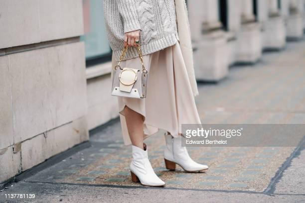 A guest wears a beige oversize knit jacket a beige handbag a beige asymmetrical skirt white boots during London Fashion Week February 2019 on...