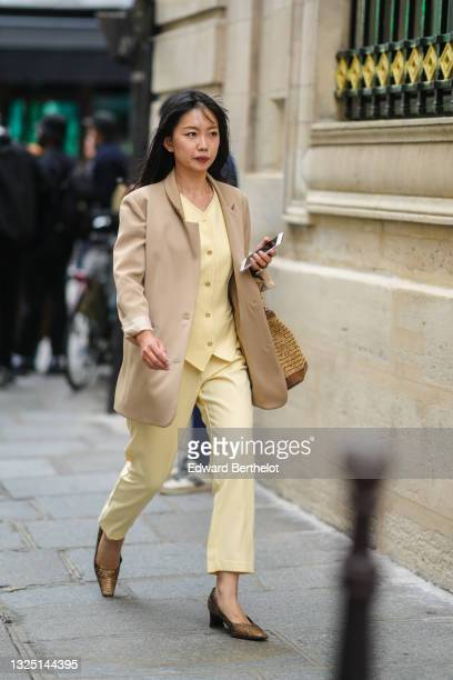 Guest wears a beige oversized blazer jacket, a pale pastel yellow double breasted top, suit pastel yellow cropped pants, brown pointed snake print...