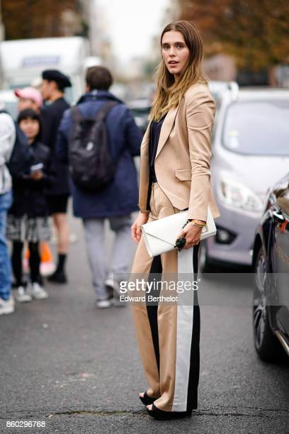 A guest wears a beige pantsuit with black and white stripes on the side a white bag platform black shoes outside Lanvin during Paris Fashion Week...