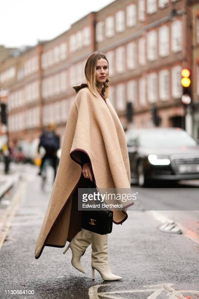 Guest wears a beige poncho, a bag, white boots, during London Fashion Week February 2019 on February 18, 2019 in London, England.