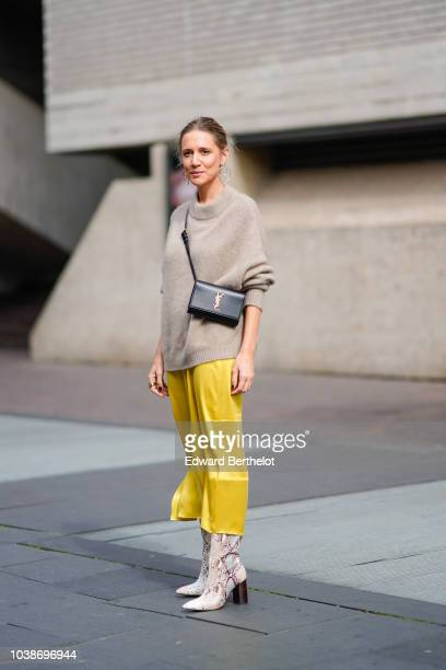 A guest wears a beige pullover a Saint Laurent YSL bag a yellow skirt snake print shoes during London Fashion Week September 2018 on September 16...