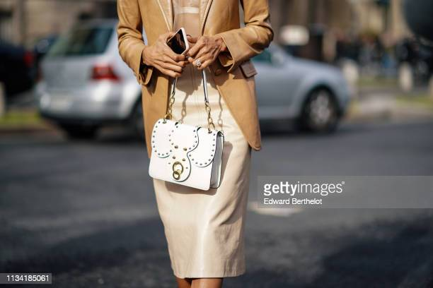 Guest wears a beige see through muslin top, a camel leather jacket, a beige leather skirt, a white Miu Miu studded bag, outside Miu Miu, during Paris...