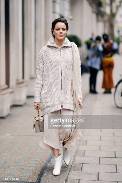 A guest wears a beige shawl a beige oversize knit jacket a beige handbag a beige asymmetrical skirt white boots during London Fashion Week February...
