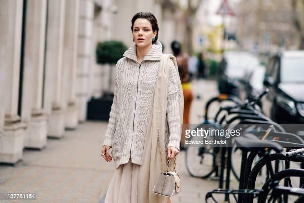 A guest wears a beige shawl a beige oversize knit jacket a beige handbag during London Fashion Week February 2019 on February 16 2019 in London...