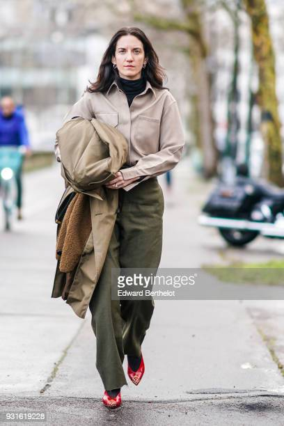 Guest wears a beige shirt,a black turtleneck top, khaki wide leg pants, red studded patent shoes, outside Valentino, during Paris Fashion Week...