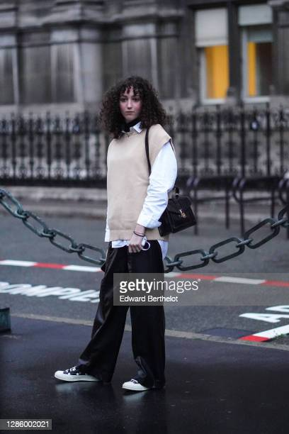 Guest wears a beige sleeveless wool pullover, a white shirt, black flared pants, sneakers shoes, a leather bag, outside Yohji Yamamoto, during Paris...