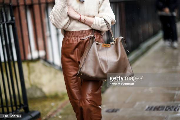 A guest wears a beige sweater brown leather pants a taupe color handbag during London Fashion Week February 2019 on February 18 2019 in London England