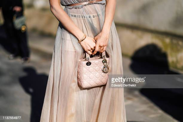 Guest wears a beige transparent tulle gathered skirt, a taupe belt with a bow, wristlets, a pale pink Lady Dior handbag, outside Dior, during Paris...