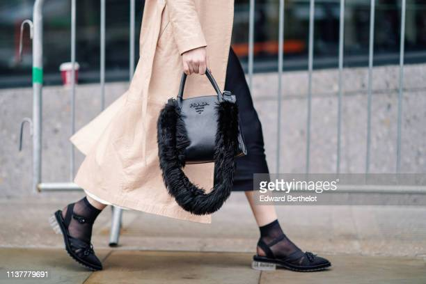 A guest wears a beige trench coat a black Prada bag with a black fur strap black pointy slingback shoes with transparent flat heel during London...