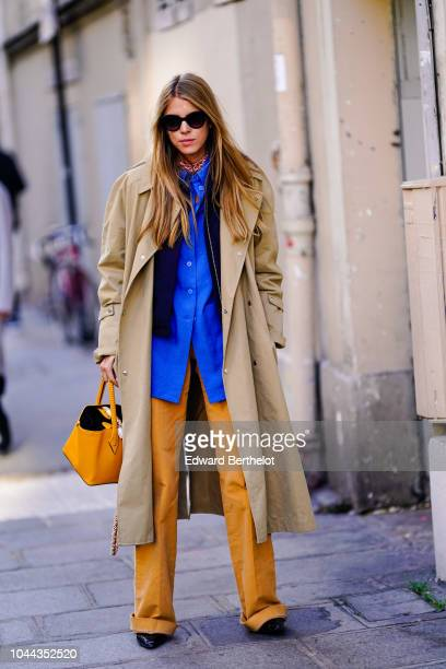 A guest wears a beige trench coat a bule shirt orange pants an orange bag outside APC during Paris Fashion Week Womenswear Spring/Summer 2019 on...