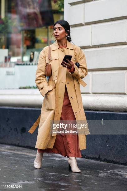 A guest wears a beige trench coat a Dior Saddle bag a brown silky dress leather shoes earrings during London Fashion Week February 2019 on February...