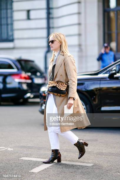 A guest wears a beige trench coat a leopard print bag white pants outside Akris during Paris Fashion Week Womenswear Spring/Summer 2019 on September...