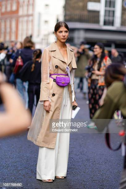 A guest wears a beige trench coat a purple belt bag white pants during London Fashion Week September 2018 on September 15 2018 in London England