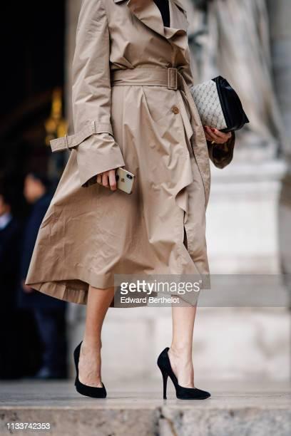 Guest wears a beige trench coat, a Stella MC Cartney bag, black pumps, outside Stella McCartney, during Paris Fashion Week Womenswear Fall/Winter...