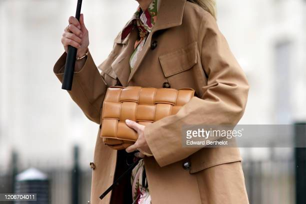 Guest wears a beige trench coat and a brown Bottega Veneta quilted bag, during London Fashion Week Fall Winter 2020 on February 16, 2020 in London,...