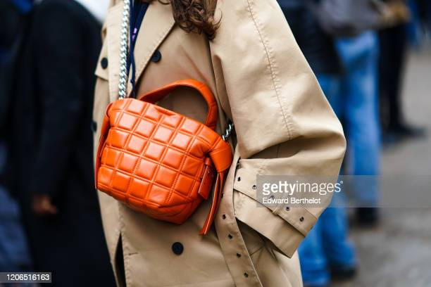 Guest wears a beige trench coat and an orange quilted bag, during London Fashion Week Fall Winter 2020, on February 15, 2020 in London, England.