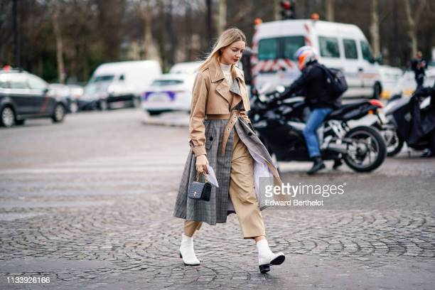 A guest wears a beige trench coat with grey Prince of Wales check insertsa black bag white ankle boots outside Chanel during Paris Fashion Week...