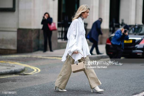 A guest wears a beige turtleneck a white flowing ruffled and gathered tunic a beige handbag beige wideleg pants beige pointy heeled boots during...