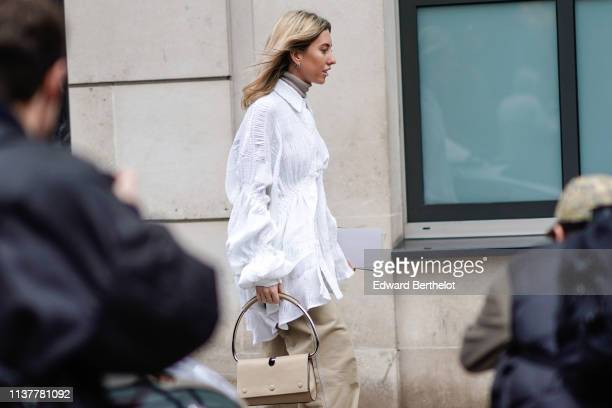 A guest wears a beige turtleneck a white flowing ruffled and gathered tunic a beige handbag beige wideleg pants during London Fashion Week February...