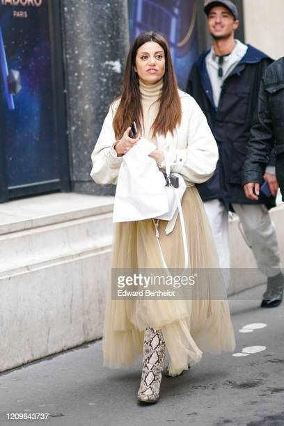 Guest wears a beige turtleneck, a white leather jacket, a beige flowing asymmetric tutu skirt, a white bag, beige and black python patterned pointy...