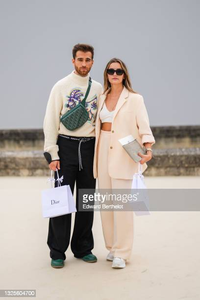 Guest wears a beige wool turtleneck pullover with purple orange and blue embroidered pattern, a dark green Dior Oblique Jacquard leather fanny pack...