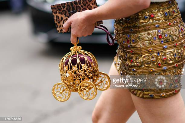 Guest wears a bejeweled golden color mini dress, a bejeweled Cinderella's carriage-shaped minaudiere, a leopard print clutch, outside the Dolce &...