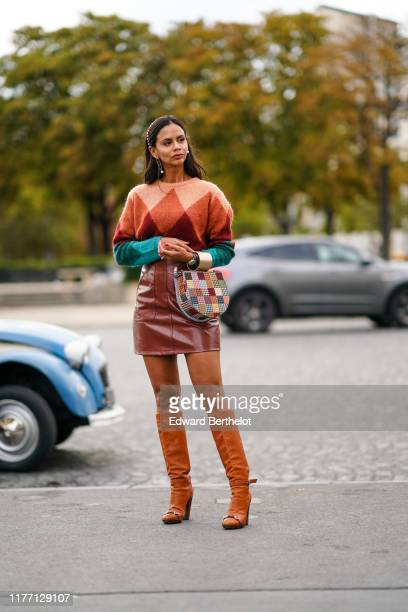 Guest wears a bejeweled headband, earrings, a colorful argyle pattern wool sweater, a brown leather mini skirt, a colorful houndstooth patchwork bag,...