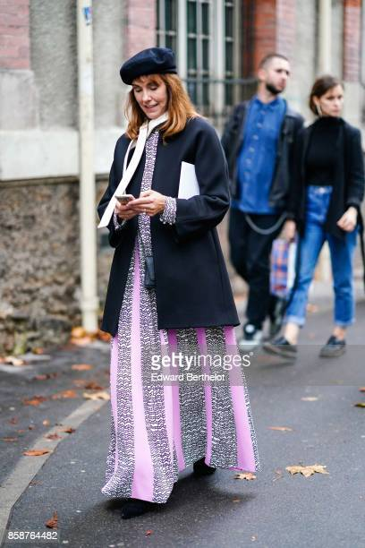 A guest wears a beret a black coat a pink and gray striped dress outside Valentino during Paris Fashion Week Womenswear Spring/Summer 2018 on October...