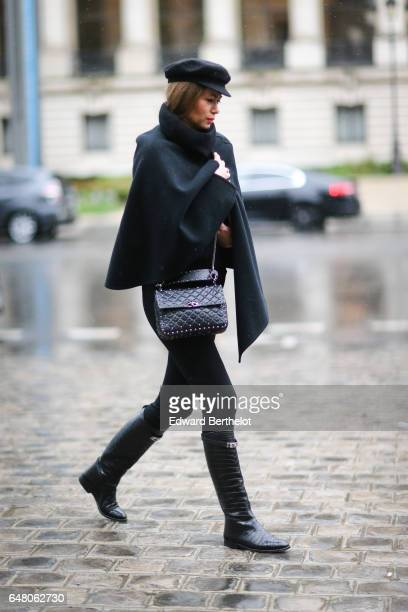 A guest wears a beret hat a black cape a black leather bag black pants and black boots outside the Elie Saab show during Paris Fashion Week...