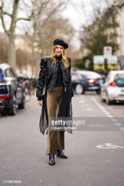 Guest wears a beret hat, a black lustrous bomber jacket with shoulder pads, a black turtleneck pullover, khaki/brown corduroy flared pants, black...