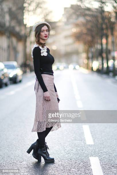 A guest wears a beret hat a black top with white flowers a lace skirt and black leather boots outside the Mashama show during Paris Fashion Week...