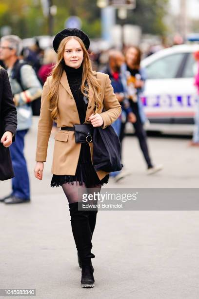 A guest wears a beret hat a brown blazer jacket black thigh high boots outside Chanel during Paris Fashion Week Womenswear Spring/Summer 2019 on...